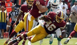 Washington Redskins running back Alfred Morris (46) tries to get away from Miami Dolphins defensive end Terrence Fede (78) who is blocked by Redskins tight end Derek Carrier (89) during the first half of an NFL football game Sunday, Sept. 13, 2015, in Landover, Md. (AP Photo/Evan Vucci)