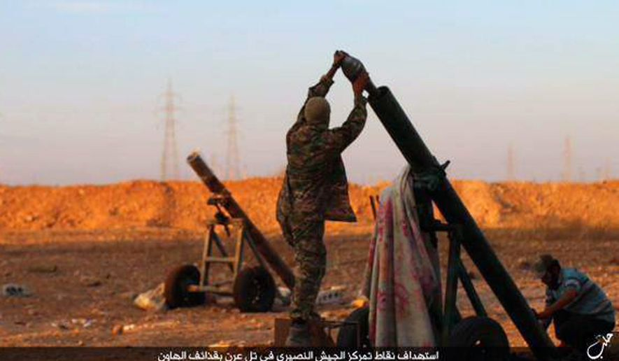 This image posted on Thursday, Oct. 8, 2015, by the Rased News Network, a Facebook page affiliated with Islamic State, shows Islamic State militants preparing to fire a mortar to shell towards Syrian government forces positions at Tal Arn in Aleppo province, Syria. (Islamic State militant website via AP)