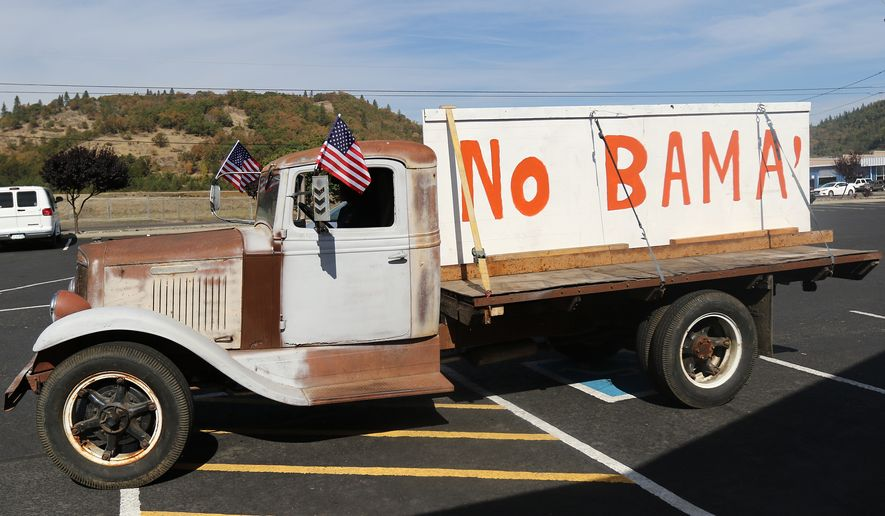Gary Shamblin of Winston, Ore., prepares to leave a parking lot in Roseburg, Ore., on Thursday Oct. 8, 2015, in his 1934 International truck displaying a sign he made reflecting his views on President Barack Obama's planned visit to the area. (Michael Sullivan /The News-Review via AP)
