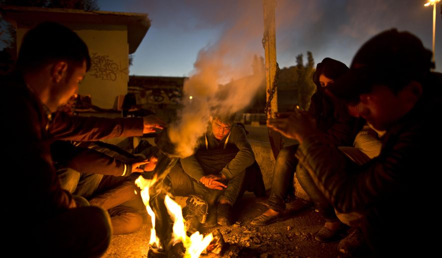Afghan refugees gather around a fire to warm themselves from the morning cold at the port of Mitylene on the northeast Greek island of Lesbos, while waiting to get on board a ferry traveling to Athens, early Friday, Oct. 9, 2015. More than 500,000 people have arrived in the European Union this year, seeking sanctuary or jobs and sparking the EU's biggest refugee emergency in decades. (AP Photo/Muhammed Muheisen)