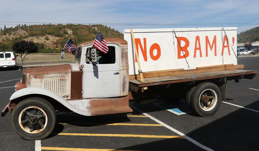 Gary Shamblin of Winston, Ore., prepares to leave a parking lot in Roseburg, Ore., on Thursday Oct. 8, 2015, in his 1934 International truck displaying a sign he made reflecting his views on President Barack Obama's planned visit to the area. (Michael Sullivan /The News-Review via AP) MANDATORY CREDIT