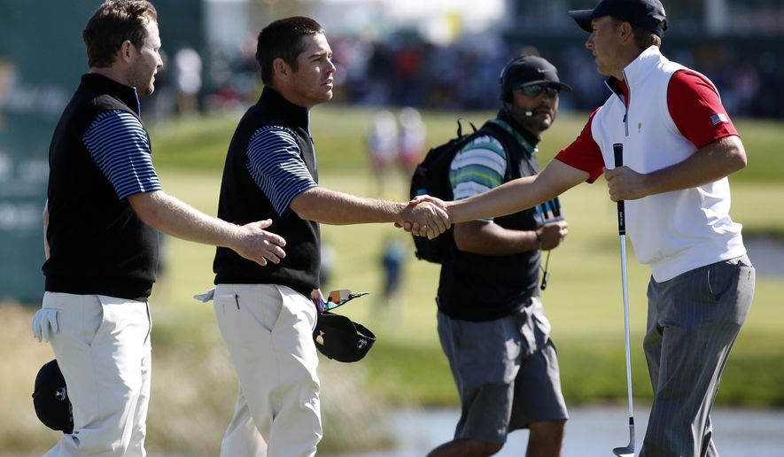 United States' Jordan Spieth, right, congratulates International team player's Louis Oosthuizen of South Africa and his teammate Branden Grace, left, on their during their 4&3 four ball win at the Presidents Cup golf tournament at the Jack Nicklaus Golf Club Korea, in Incheon, South Korea, Friday, Oct. 9, 2015.(AP Photo/Lee Jin-man)