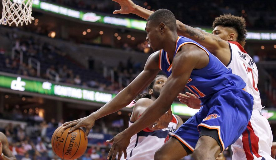 New York Knicks forward Cleanthony Early (11) passes in front of Washington Wizards forward Nene, left, from Brazil, and Washington Wizards forward Kelly Oubre Jr. in the first half of an NBA preseason basketball game, Friday, Oct. 9, 2015, in Washington. (AP Photo/Alex Brandon)