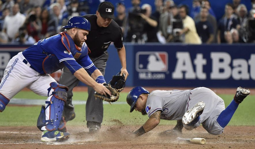 Toronto Blue Jays' catcher Russell Martin, left, attempts to tag Texas Rangers' Rougned Odor, right, who scores during the 14th inning of baseball Game 2 of the American League Division Series in Toronto, Friday, Oct. 9, 2015. (Nathan Denette/The Canadian Press via AP) MANDATORY CREDIT