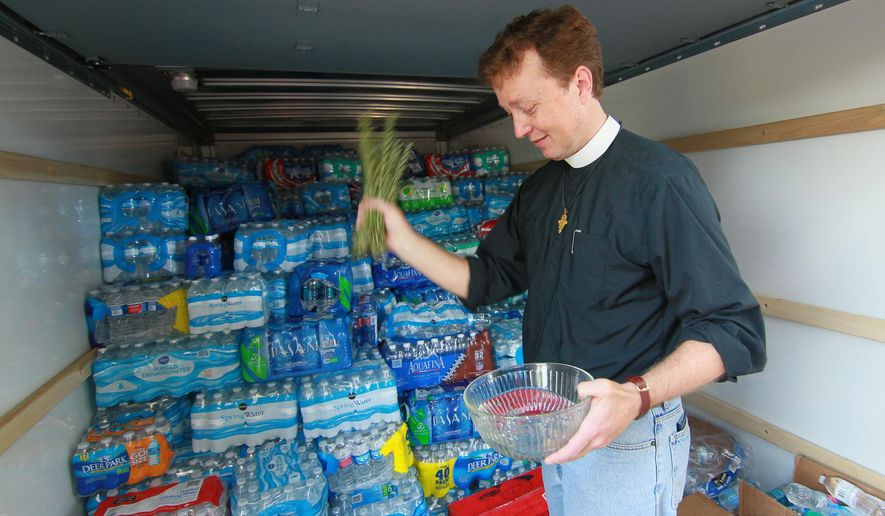 Father Jack Hardaway of Grace Episcopal Church blesses water delivered from The Holy Innocents' Episcopal School in Atlanta to help flood victims in Anderson, S.C., on Thursday, Oct. 8, 2015. A number of South Carolina residents near the coast are evacuating and others are piling up sandbags anew outside homes and businesses, bracing for more possible flooding even as the nation's Homeland Security chief is set later Friday to tour areas hit hard by recent heavy rains. (Ken Ruinard/The Independent-Mail via AP) THE GREENVILLE NEWS OUT, SENECA NEWS OUT; MANDATORY CREDIT