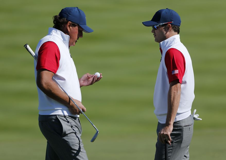 United States' Phil Mickelson, left, and teammate Zach Johnson chat on the second hole during their four ball match at the Presidents Cup golf tournament at the Jack Nicklaus Golf Club Korea, in Incheon, South Korea, Friday, Oct. 9, 2015.(AP Photo/Woohae Cho)