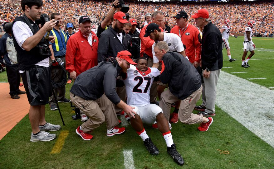 Georgia running back Nick Chubb is helped off the field after injuring his left knee on the first play from scrimmage during an NCAA college football game against Tennessee, Saturday, Oct. 10, 2015, in Knoxville, Tenn.  (Brant Sanderlin/Atlanta Journal-Constitution via AP)  MARIETTA DAILY OUT; GWINNETT DAILY POST OUT; LOCAL TELEVISION OUT; WXIA-TV OUT; WGCL-TV OUT; MANDATORY CREDIT