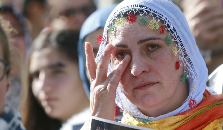 A Kurdish demonstrator in Paris, cries as she and others gather after an explosion at a rally in Ankara, Turkey, Saturday, Oct. 10, 2015. Turkey's health minister says two bomb explosions in the Turkish capital have killed scores of people. The explosions occurred minutes apart near Ankara's main train station as people were gathering for a rally, organized by the country's public sector workers' trade union and other civic society groups. The rally aimed to call for an end to the renewed violence between Kurdish rebels and Turkish security forces. (AP Photo/Jacques Brinon)