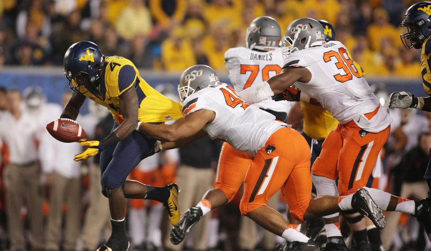 West Virginia running back Wendell Smallwood (4) loses the football while being tackled by Oklahoma State linebacker Chad Whitener (45) during the first half of an NCAA college football game, Saturday, Oct. 10, 2015, in Morgantown, W.Va. (AP Photo/Raymond Thompson)