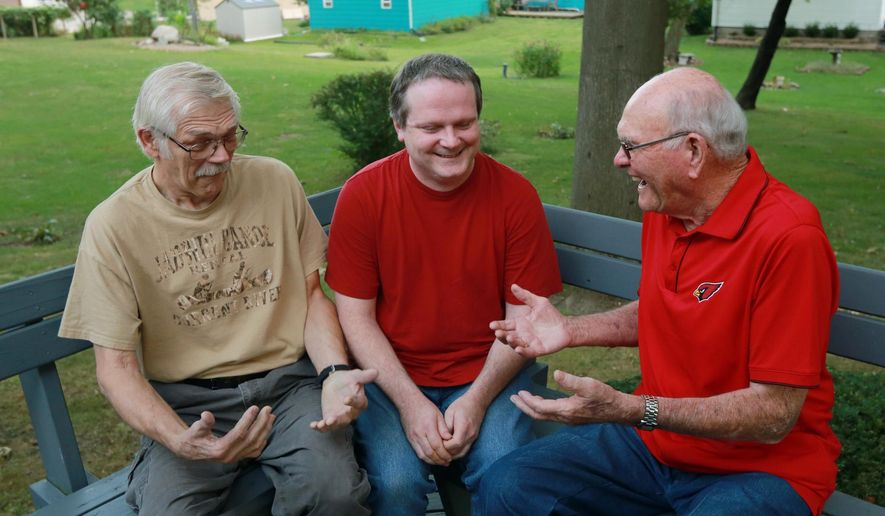 Richard Hand, center, talks with former Bentler 66 gas station attendant Bob Derr, left and gas station owner Tony Bentler, on Sept. 22, 2015 at Bentler's Mount Pleasant, Iowa, home. Hand was born in the gas station restroom on Oct. 4, 1970, after his mother made a stop to use the facility.  (John Lovretta/The Hawk Eye via AP) MANDATORY CREDIT (REV-SHARE)