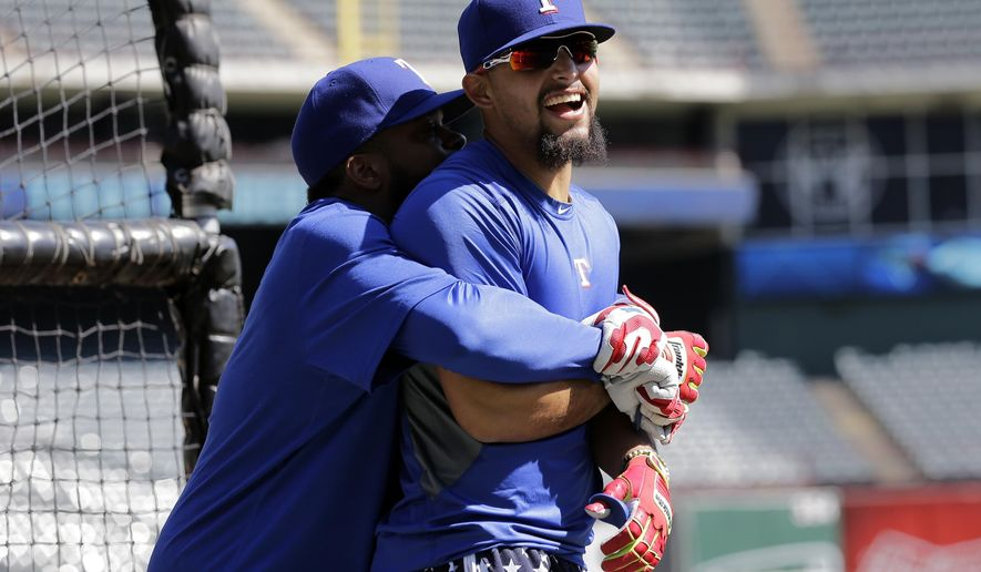 Texas Rangers' Rougned Odor, right, is grabbed by teammate Delino DeShields, left, as they joke during an American League Division Series baseball practice, Saturday, Oct. 10, 2015, in Arlington, Texas. The Rangers will face the Toronto Blue Jays in game 3 Sunday. (AP Photo/Eric Gay)