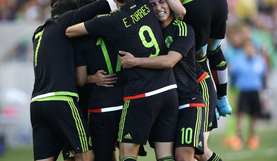 Members of the Mexico team celebrate with Hirving Lozano after scoring against Canada during the second half of a CONCACAF men's Olympic semifinal soccer match Saturday, Oct. 10, 2015, in Sandy, Utah. Mexico won 2-0. (AP Photo/Rick Bowmer)