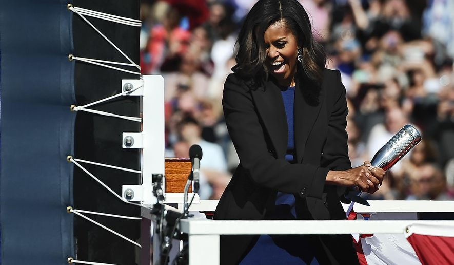 First lady Michelle Obama christens the USS Illinois with a bottle of sparkling wine at Electric Boat, a division of General Dynamics, shipyard, Saturday, Oct. 10, 2015, in Groton, Conn. The $2.7 billion vessel is the 13th in the Virginia class of submarines, which can carry out a range of missions including anti-submarine warfare, delivery of special forces, and surveillance.  (AP Photo/Jessica Hill)
