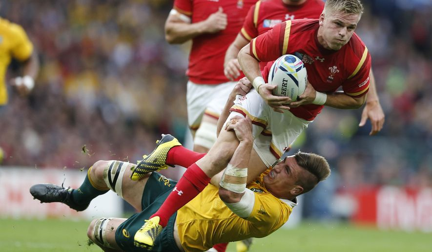 Wales' Gareth Anscombe is tackled by Australia's Sean McMahon during the Rugby World Cup Pool A match between Australia and Wales at Twickenham Stadium, London, Saturday, Oct. 10, 2015. (AP Photo/Frank Augstein)