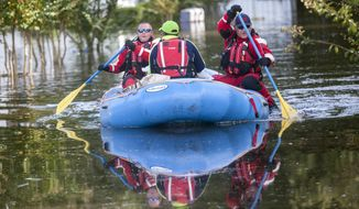 Firefighters evacuate Eliza Linen by boat from her home in the Dunbar Community of Georgetown, S.C., Friday, Oct. 9, 2015. A week after the heavy rains first began, some South Carolina residents are still evacuating and others are stacking up sandbags for more possible flooding even as the nation's top security official prepares to inspect the damage firsthand. (Jason Lee/The Sun News via AP)
