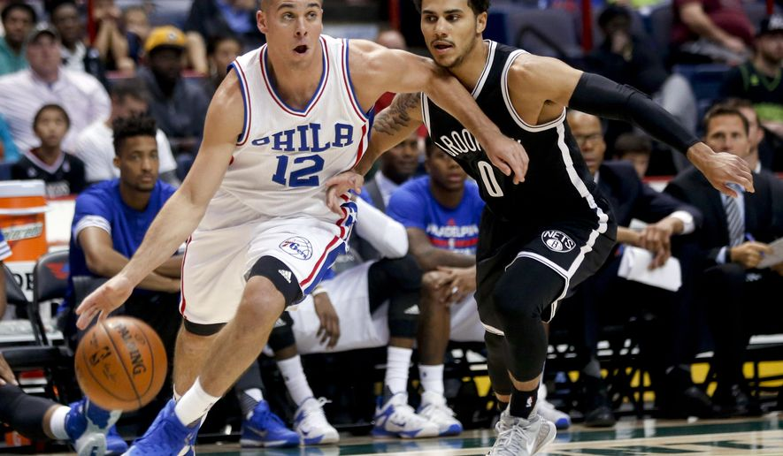 Philadelphia 76ers guard T.J. McConnell (12) drives past Brooklyn Nets guard Shane Larkin (0) during the first half of an NBA preseason basketball game, Saturday, Oct. 10, 2015, in Albany, N.Y. (AP Photo/Mike Groll)