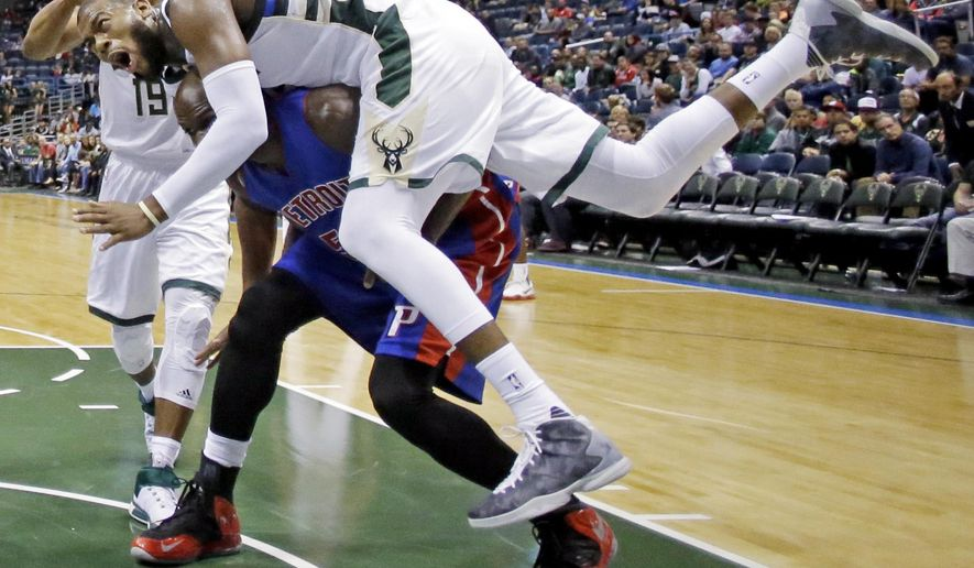 Milwaukee Bucks' Greg Monroe (15) lands on Detroit Pistons' Joel Anthony as he goes up for a rebound during the second half of an NBA preseason basketball game Saturday, Oct. 10, 2015, in Milwaukee. (AP Photo/Morry Gash)