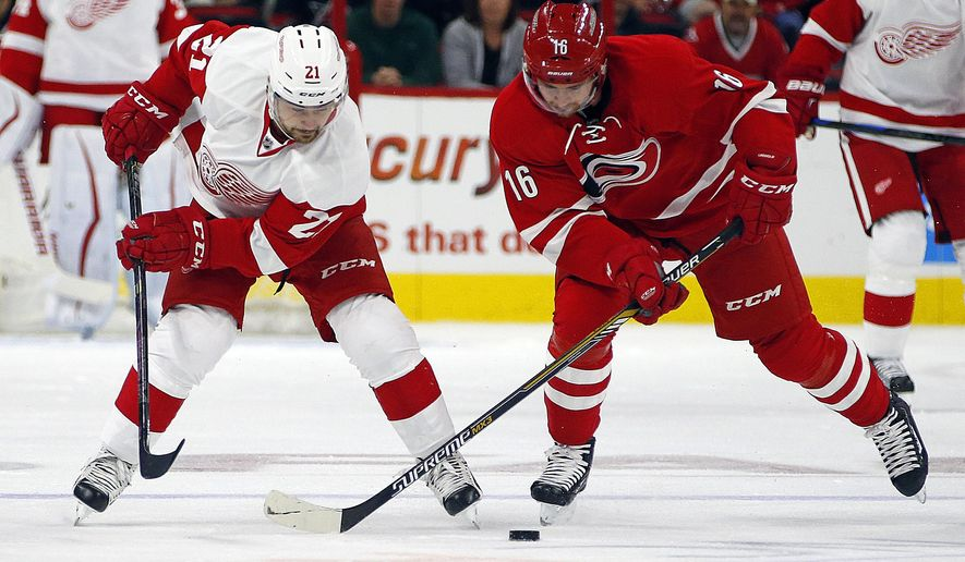 Detroit Red Wings' Tomas Tatar (21) battles with Carolina Hurricanes' Elias Lindholm (16) of Sweden, during the first period of an NHL hockey game, Saturday, Oct. 10, 2015, in Raleigh, N.C. (AP Photo/Karl B DeBlaker)