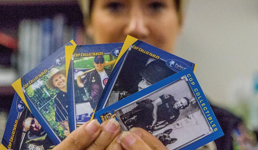 In this photo taken on Sept. 30, 2015, a selection of the Paducah Police Department Community Resource Officer Gretchen Morgan holds up a few of the new KPD baseball-style cards Paducah, Ky. Discontinued about 12 years ago due to budget constraints, the new cards, paid for by Head Start as part its community partnership efforts, will be hitting the streets in the next few weeks.  (Kat Russell/The Paducah Sun via AP) MANDATORY CREDIT
