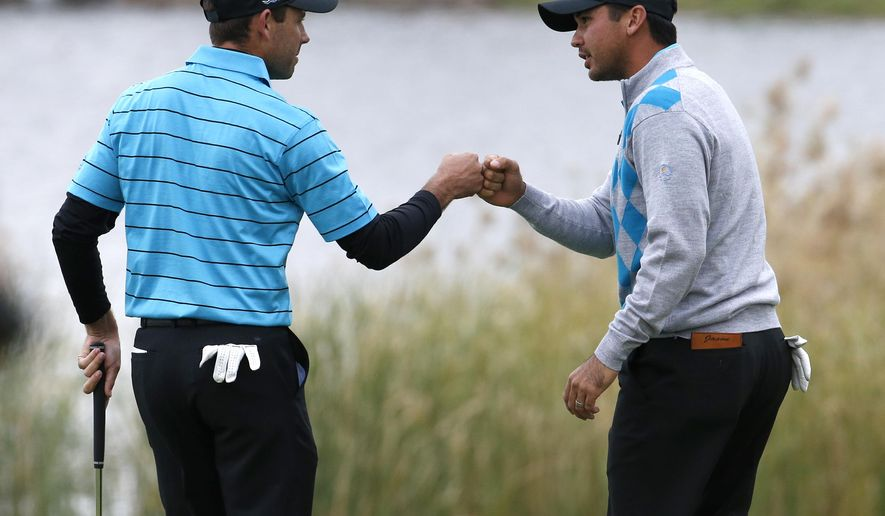 International team player Jason Day, right, of Australia congratulates partner Charl Schwartzel of South Africa during their foursome match at the Presidents Cup golf tournament at the Jack Nicklaus Golf Club Korea, in Incheon, South Korea, Saturday, Oct. 10, 2015.(AP Photo/Lee Jin-man)