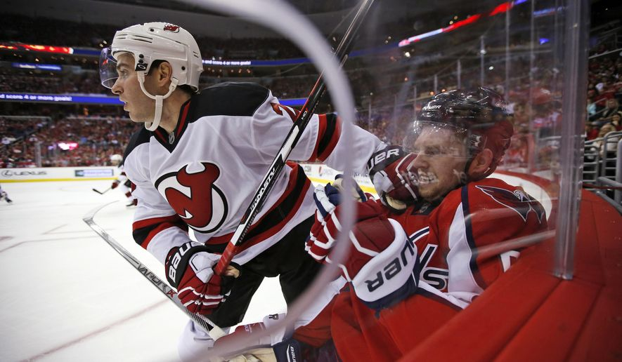 New Jersey Devils defenseman John Moore (2) pushes off Washington Capitals defenseman Dmitry Orlov, from Russia, during the second period of an NHL hockey game, Saturday, Oct. 10, 2015, in Washington. (AP Photo/Alex Brandon)
