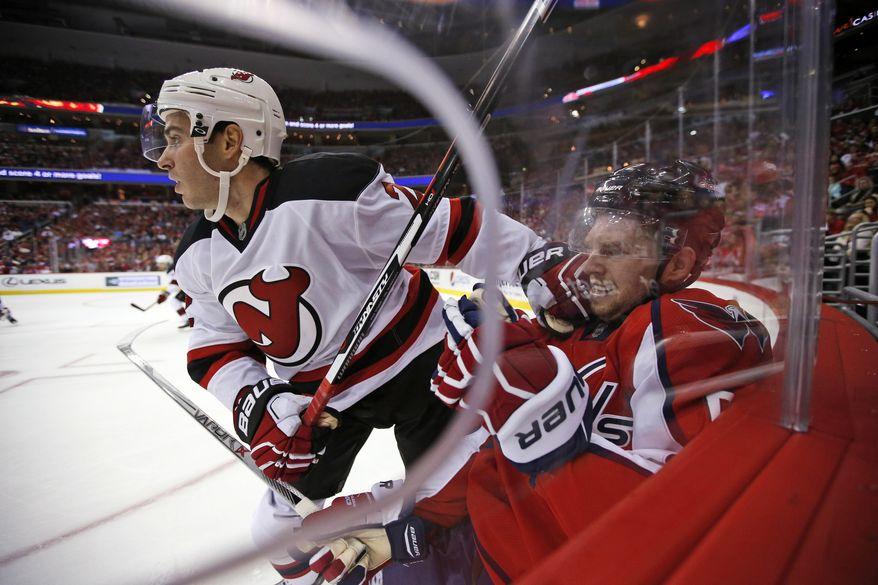 New Jersey Devils defenseman John Moore (2) pushes off Washington Capitals defenseman Dmitry Orlov, from Russia, during the second period of an NHL hockey game, Saturday, Oct. 10, 2015, in Washington. (AP Photo/Alex Brandon)