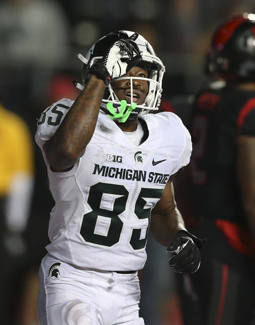 Michigan State wide receiver Macgarrett Kings Jr. (85) celebrates after scoring a touchdown during the first half of an NCAA college football game against Rutgers, Saturday, Oct. 10, 2015, in Piscataway, N.J. (AP Photo/Mel Evans)