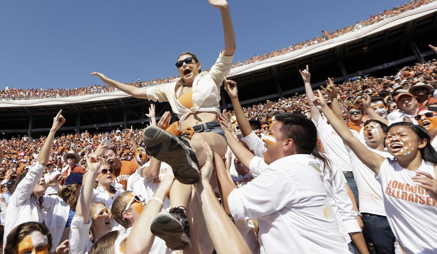 Texas fans toss one of their own into the air during the second half of an NCAA college football game against Oklahoma Saturday, Oct. 10, 2015, in Dallas. (AP Photo/LM Otero)