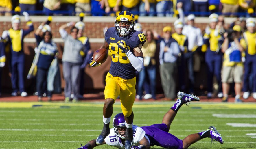 Michigan wide receiver Jehu Chesson (86) evades a tackle from Northwestern safety Godwin Igwebuike (16) as he returns the opening kickoff 96 yards for a touchdown during the first quarter of an NCAA college football game in Ann Arbor, Mich., Saturday, Oct. 10, 2015. (AP Photo/Tony Ding)