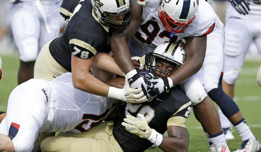 Central Florida running back C.J. Jones, bottom center, is stopped by the Connecticut defense on the 1-yard line during the first half of an NCAA college football game, Saturday, Oct. 10, 2015, in Orlando, Fla. (AP Photo/John Raoux)