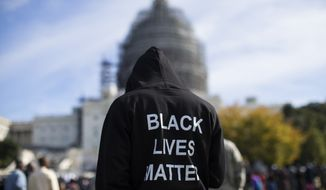 "Neal Blair, of Augusta, Ga., wears a hoodie which reads, ""Black Lives Matter"" as stands on the lawn of the Capitol building during a rally to mark the 20th anniversary of the Million Man March, on Capitol Hill, on Saturday, Oct. 10, 2015, in Washington. Black men from around the nation returned to the capital calling for changes in policing and in black communities. (AP Photo/Evan Vucci) ** FILE **"