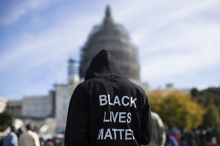 """Neal Blair, of Augusta, Ga., wears a hoodie which reads, """"Black Lives Matter"""" as stands on the lawn of the Capitol building during a rally to mark the 20th anniversary of the Million Man March, on Capitol Hill, on Saturday, Oct. 10, 2015, in Washington. Black men from around the nation returned to the capital calling for changes in policing and in black communities. (AP Photo/Evan Vucci) ** FILE **"""