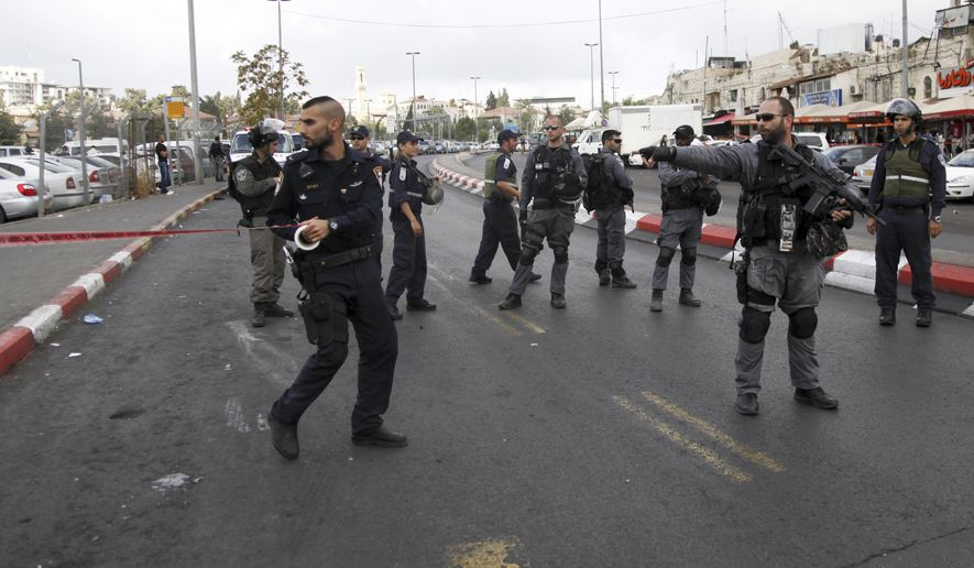 Israeli police secure the scene of a stabbing attack in Jerusalem Saturday, Oct. 10, 2015. A Palestinian teenager stabbed two Israelis in Jerusalem Saturday before being shot dead by police forces, the latest in a series of stabbing attacks against civilians and soldiers that have spread across Israel and the West Bank in the past week. (AP Photo/Mahmoud Illean)