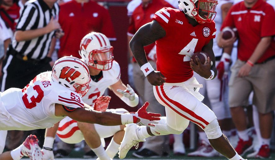 Nebraska quarterback Tommy Armstrong Jr. (4) runs away from a tackle by Wisconsin linebacker T.J. Edwards (53) during the first half of an NCAA college football game in Lincoln, Neb., Saturday, Oct. 10, 2015. (AP Photo/Nati Harnik)