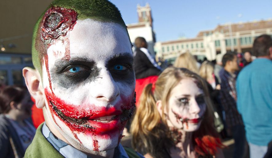 Joe Marrero and Christina Twidle strolls down the Asbury Park Boardwalk during Zombie Walk in Asbury Park, N.J., Saturday, Oct. 10, 2015. Participants planned to make an extended walk through the city, then remain in the area for festivities that start once the sun goes down. (Doug Hood/The Asbury Park Press via AP)  NO SALES; MANDATORY CREDIT
