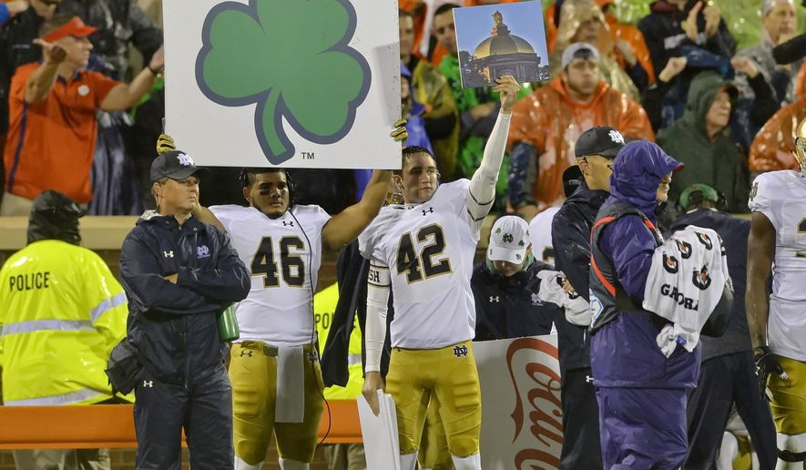 FILE - In this Oct. 3, 2015, file photo, Notre Dame players hold up signs during the first half of an NCAA college football game against Clemson in Clemson, S.C.  Once a technique used to replace hand signals for offenses, in the past few years, defenses have started using them, too.  (AP Photo/Richard Shiro, File)