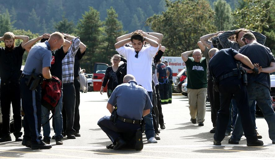 FILE - This Oct. 1, 2015, file photo shows police searching students outside Umpqua Community College in Roseburg, Ore., following a deadly shooting at the college. Despite a federal law requiring them to have detailed emergency plans, colleges and universities across the country vary widely in how they prepare for campus shootings and inform their staff and students. (Mike Sullivan/Roseburg News-Review via AP,File)