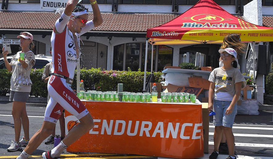 Jan Frodeno, of Germany, pours water on his head during the marathon portion of the Ironman World Championship Triathlon, Saturday, Oct. 10, 2015, in Kailua-Kona, Hawaii. (AP Photo/Mark J. Terrill)