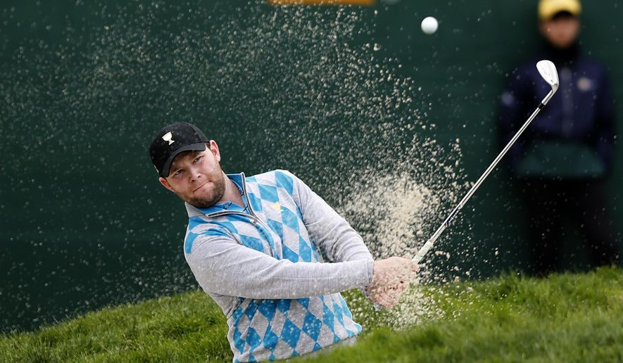 International team player Branden Grace of South Africa plays from a bunker on the 16th hole during his foursome match at the Presidents Cup golf tournament at the Jack Nicklaus Golf Club Korea, in Incheon, South Korea, Saturday, Oct. 10, 2015.(AP Photo/Woohae Cho)