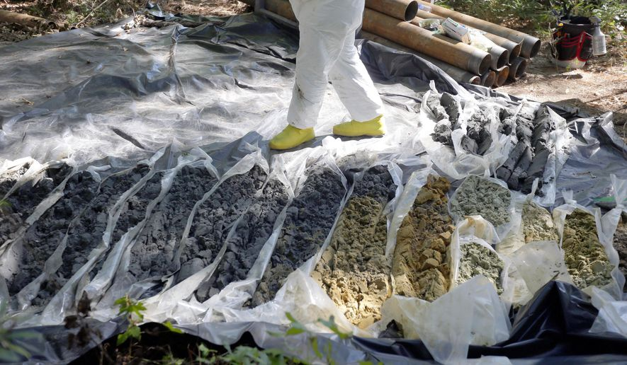 In this photo taken Tuesday, Sept. 15, 2015, soil samples are collected at a Superfund site in Navassa, N.C., where the federal government is tasked with repairing environmental damage caused by creosote used at a wood treatment plant that closed in the 1970s. The site is being cleaned up under a $5 billion settlement of a nationwide environmental-legal case known as the Anadarko litigation, reached by the U.S. Justice Department.   (AP Photo/Gerry Broome)