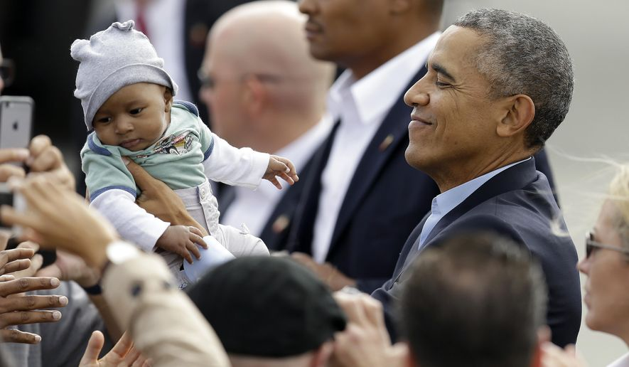President Barack Obama holds a baby prior to boarding Air Force One Saturday, Oct. 10, 2015, in San Francisco. Obama will arrive in Los Angeles, Calif., later today. (AP Photo/Ben Margot)