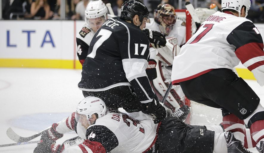 Los Angeles Kings' Milan Lucic, top, takes a tumble over Arizona Coyotes' Klas Dahlbeck, of Sweden, during the second period of an NHL hockey game, Friday, Oct. 9, 2015, in Los Angeles. (AP Photo/Jae C. Hong)