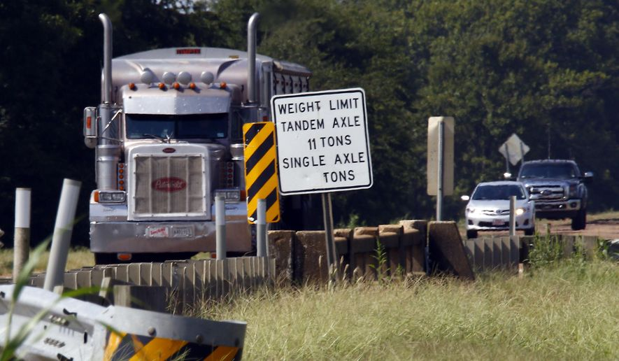 In this Sept. 11, 2015 photo, a commercial truck passes over the bridge at Bobo Bayou on Mississippi Highway 6, near Batesville, Miss. The sign on the bridge shows the weight limitations established by the state for commercial and farm vehicles, but overuse, illegal heavier loads and increased traffic have taken their toll on this and many other of the state's bridges. The state of Mississippi's roads and bridges are an election issue this fall. (AP Photo/Rogelio V. Solis)