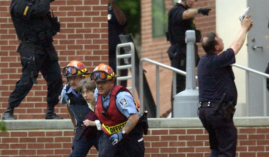 """FILE - In this file photo taken May 9, 2003, police cover Cleveland Emergency Medical Service personnel escorting a woman out of a building at Case Western Reserve University in Cleveland, where 62-year-old former graduate student, Biswanath Halder, killed 30-year-old graduate student Norman Wallace of Youngstown, Ohio, and wounded two others during a 7 1/2-hour siege. A 2015 review by The Associated Press finds that eight years after the Virginia Tech massacre led to tighter security at U.S. colleges, some schools make """"active shooter"""" training mandatory for incoming students, and Ohio takes a hands-off approach by leaving policies up to schools to develop. (AP Photo/Mark Duncan, File)"""