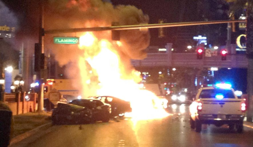 FILE - In this Feb. 21, 2013 file photo, smoke and flames billow from a burning vehicle following a shooting and multi-car accident on the Las Vegas Strip in Las Vegas. Jury selection in the death-penalty trial for 29-year-old Ammar Harris, a self-described pimp accused of killing three people in the shooting and crash that witnesses compared to a scene from a Hollywood action movie, begins Monday, Oct. 12, 2015. (AP Photo/Erik Lackey, File)