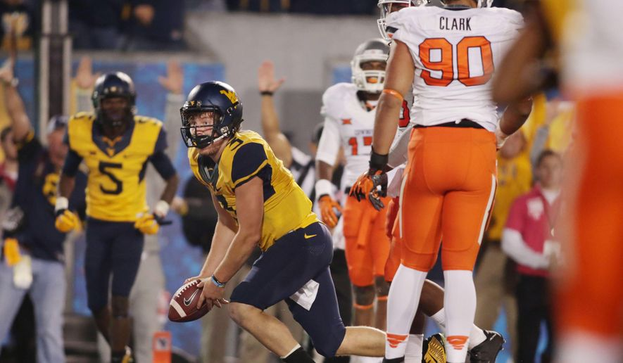 West Virginia quarterback Skyler Howard (3) runs the ball for a touchdown during the second half of an NCAA college football game against Oklahoma State, Saturday, Oct. 10, 2015, in Morgantown, W.Va. Oklahoma State defeat West Virginia 33-26 in overtime. (AP Photo/Raymond Thompson)