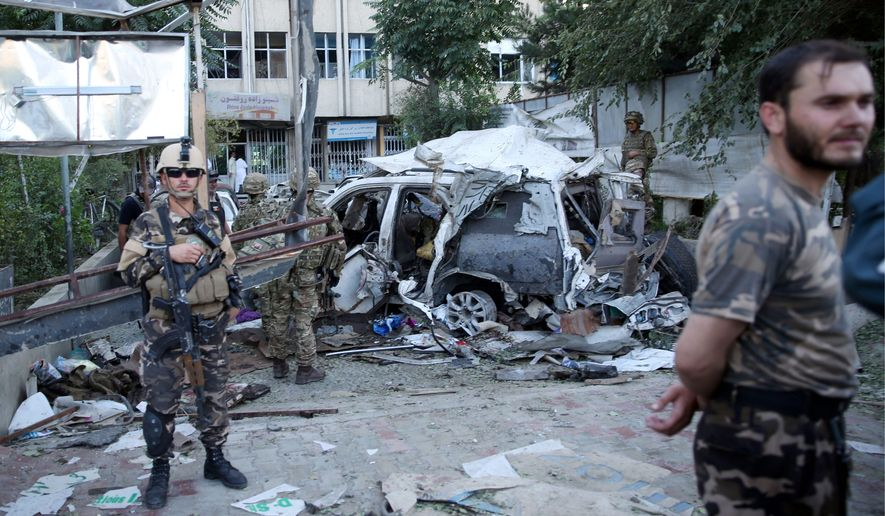 Afghan security forces and British soldiers inspect the site of a suicide attack in the heart of Kabul, Afghanistan. Loyalists of the Islamic State group are making inroads into Afghanistan, with homegrown militants claiming allegiance to the Islamic State as it controls territory in some parts of the country. (Associated Press)