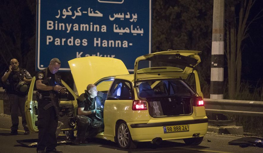 Israeli police inspects a car used in an attack by Israeli Arab near the town of Hadera, Israel, Sunday, Oct. 11, 2015. An Arab citizen of Israel stabbed four Israelis, seriously injuring a 19-year-old woman, before Israeli police apprehended him, police spokesman said. (AP Photo/Oren Ziv)