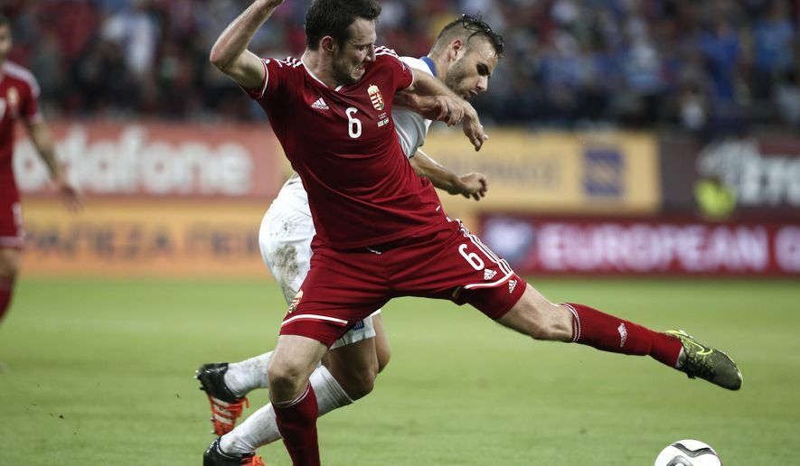 Hungary's Akos Elek, front, is challenged by Greece's Alexandros Tziolis during the group F Euro 2016 qualifying match between Greece and Hungary at the Georgios Karaiskakis stadium in Piraeus port, near Athens, Sunday, Oct. 11, 2015. (AP Photo/Yorgos Karahalis)