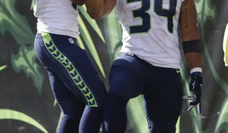 Seattle Seahawks running back Thomas Rawls (34) celebrates his touchdown with wide receiver Tyler Lockett, left, in the second half of an NFL football game against the Cincinnati Bengals, Sunday, Oct. 11, 2015, in Cincinnati. (AP Photo/Gary Landers)